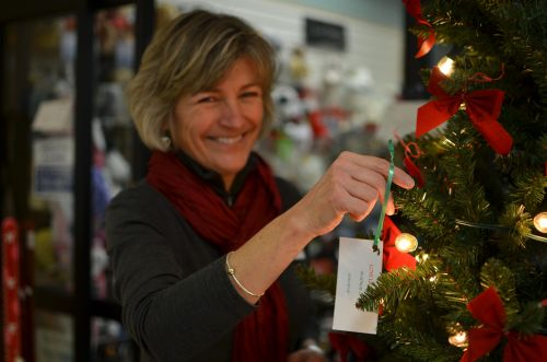 Central Vermont Medical Center Auxiliary President Heidi Pelletier hangs a donor tag on the Lovelight Tree in CVMC's lobby.