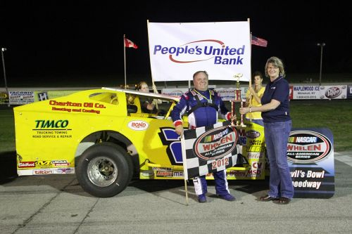 Bond Auto Parts Modified champion Ron Proctor (left) celebrates his People's United Bank Memorial Day Special victory with Sharon Kendall (right) of People's United Bank in Fair Haven, VT at Devil's Bowl Speedway in 2012.  (MemorEvents photo)