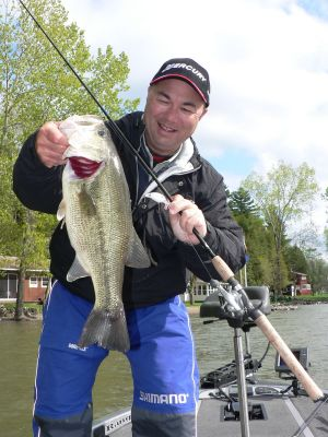 """Photo courtesy of VT Fish & Wildlife:   Canadian angler Bob Izumi with a nice largemouth bass he caught and released in an earlier visit to Lake Champlain.  Based in Ontario, Izumi hosts the """"Real Fishing Show"""" seen on TV throughout Canada."""
